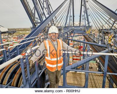 Dock supervisor on crane above cargo ship at the end of long walkway ship - Stock Photo