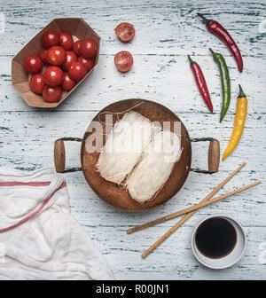 concept preparation of Funchoza with hot pepper, tomatoes and soy sauce, on a light rustic wooden background, space for text - Stock Photo