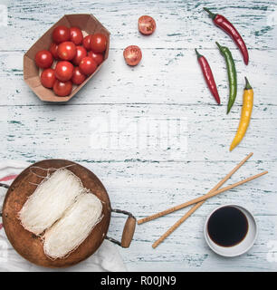concept cooking Funchoza with hot pepper, tomatoes and soy sauce, lined with a frame on a light rustic wooden background, space for text - Stock Photo