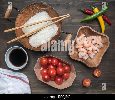 Preparation of Funchoza with shrimps, hot peppers, tomatoes and soy sauce, on rustic wooden background, top view - Stock Photo
