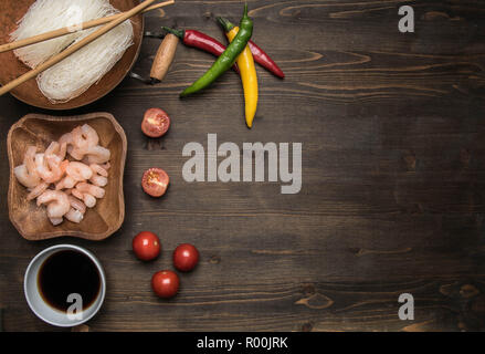 Preparation of Funchoza with shrimps, hot peppers, tomatoes and soy sauce, on rustic wooden background, space for text - Stock Photo
