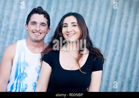Teenage boy and girl standing close looking at the camera smiling - Stock Photo