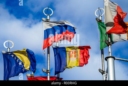 Flags of European countries on flagpoles against the blue sky. - Stock Photo