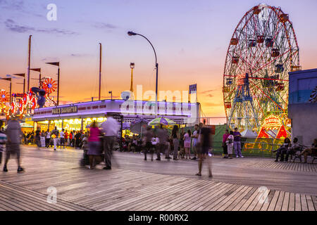 oney Island boardwalk in Brooklyn with amusement park rides - Stock Photo
