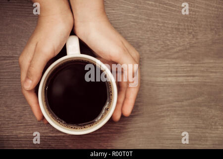 a cup of coffee in your hands on wooden background. - Stock Photo