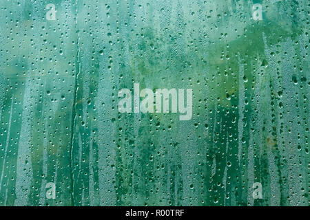 The surface of polyethylene film with a condensed drops of dew on the fuzzy background of green plants - Stock Photo