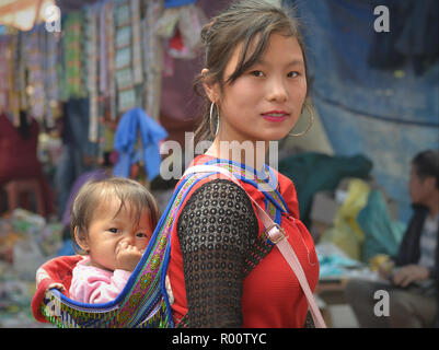Young Vietnamese Flower H'mong hill-tribe beauty carries on her back a nose-picking baby girl in an embroidered traditional baby sling. - Stock Photo
