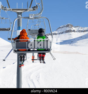 Two skiers go up on chair-lift and snowy ski slope at sunny winter day. Caucasus Mountains, Georgia, region Gudauri. - Stock Photo