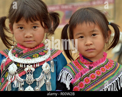 Two little Vietnamese Flower H'mong ethnic minority girls with a silver necklace, clad in colourful, embroidered traditional H'mong attire. - Stock Photo