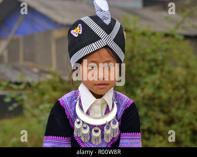 Little Vietnamese Black H'mong girl with traditional Miao/H'mong hat and in tribal attire with silver necklace. - Stock Photo