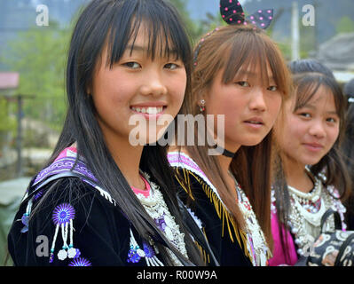 Three Vietnamese Black H'mong hill-tribe teenage girls in traditional attire. - Stock Photo