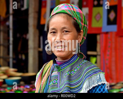 Vietnamese Flower H'mong ethnic-minority hill-tribe woman with a distinctive tribal gold tooth and heavy silver earrings poses for the camera. - Stock Photo