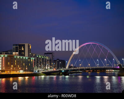 Looking at the Squinty Bridge at night from the Bells Bridge in Glasgow Waterfront District, with the Light Reflections on the water of the River Clyd - Stock Photo