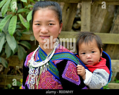 Young Vietnamese Flower H'mong hill-tribe woman wears her clan's traditional embroidered outfit and carries her baby son in a baby sling on her back. - Stock Photo