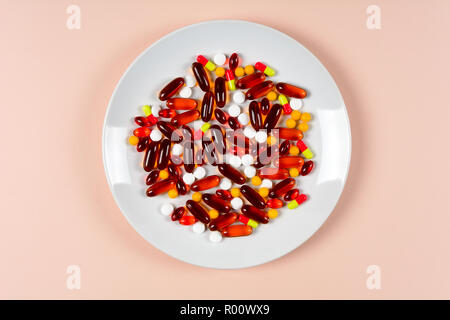 Colorful capsules and pills on plate on pink background. Health care or synthetic food concept. Top view - Stock Photo