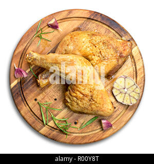 Delicious roast chicken legs or chicken drumsticks on a wooden cutting board. High angle view and fresh rosemary and garlic. Isolated on white backgro - Stock Photo