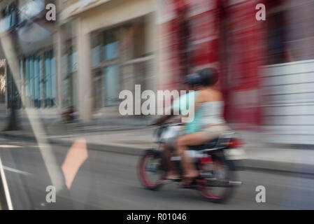 A couple speeds by on a motorcycle in Havana, Cuba. - Stock Photo