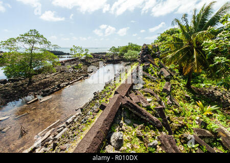 Walls and canals of Nandowas part of Nan Madol - overgrown prehistoric ruined stone city, palms. Pohnpei, Micronesia, Oceania. Venice of the Pacific - Stock Photo