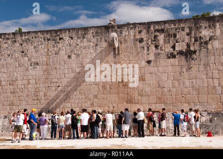 Tourists view the Great Ball Court (Gran Juego de Pelota), used to play a Mesoamerican ballgame, at Chichen Itza, Yucatan, Mexico. - Stock Photo
