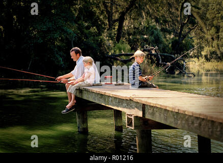 Father fishing off lake pier with his son and daughter - Stock Photo