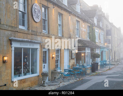 The Old Stocks Inn in the early morning autumn fog, Stow on the Wold, Gloucestershire, Cotswolds, England - Stock Photo