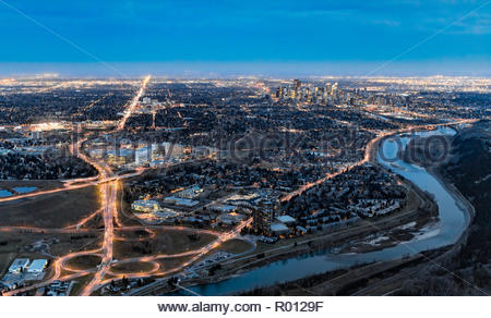 Aerial night photo showing Calgary Foothills hospital complex, the city centre and Bow River. - Stock Photo