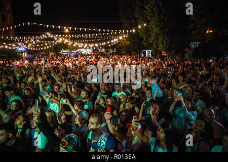 KIEV-11 JULY,2018: Group of young people partying on summer hip hop music festival Bazar outdoor.Concert crowd enjoy the show at night.Fans take pictu - Stock Photo
