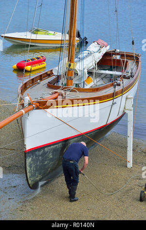 Power washing the hull of a Falmouth Working Boat on the beach at St Mawes, Roseland Peninsula, Cornwall, South West England, UK - Stock Photo