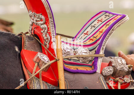 Closeup of colorful traditional Russian saddle with silver metal engravings on horse in Mongolia - Stock Photo