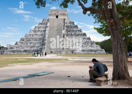 Tourists visit El Castillo, also known as the Temple of Kukulcan, a step-pyramid at Chichen Itza, Mexico. - Stock Photo