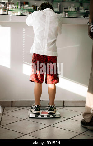 Rear view of a small boy checking his weight through the scale. - Stock Photo
