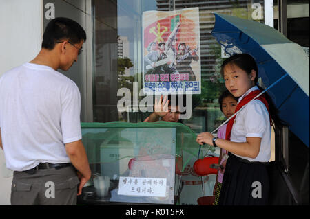 Pjoengjang, North Korea, An ice cream seller in front of a department store in the North Korean capital - Stock Photo