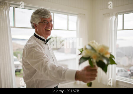 Smiling mature man holding a bouquet of flowers inside a room in his house. - Stock Photo