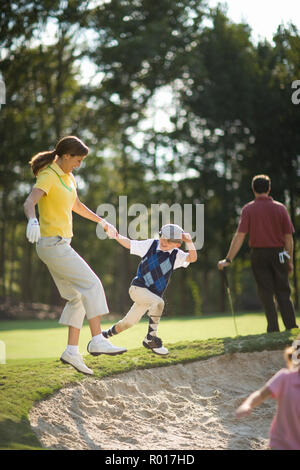 Young boy pulling his mid-adult mother into a sandpit on a golf course. - Stock Photo