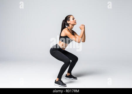 Image of sporty athletic woman in sneakers and tracksuit squatting doing sit-ups in gym isolated over gray background - Stock Photo