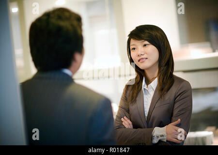 Young businesswoman speaking with a male colleague. - Stock Photo