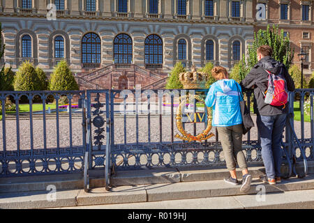 16 September 2018: Stockholm, Sweden - Young couple sightseeing at the gates of the Royal Palace. - Stock Photo