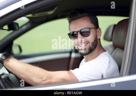stylish young man driving a convertible car - Stock Photo