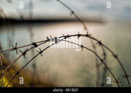 Barbed wire, Pointe du Hoc, Normandy. Pointe du Hoc is a promontory with a 100 ft (30 m) cliff overlooking the English Channel on the coast of Normand - Stock Photo