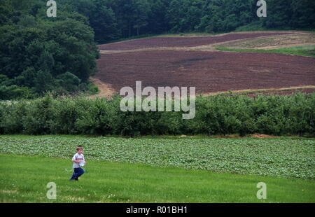 A Jewish kid running across a field to get to the fruit picking orchards. - Stock Photo
