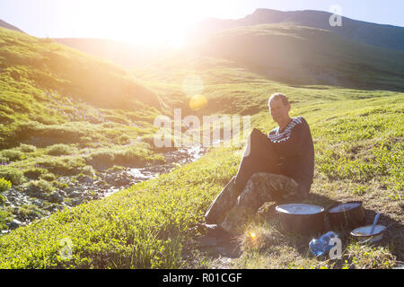 A man traveler puts things in a backpack sitting on the river bank. - Stock Photo
