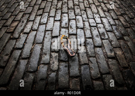 womens beaded slip on shoe discarded on dark cobbled street - Stock Photo