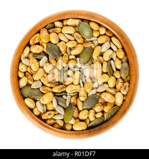 Snack mix in wooden bowl. Dried soya beans, pumpkin seeds and sunflower seeds, crispy roasted and slightly salted, used as snack. - Stock Photo