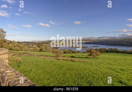 Classic view of the Menai Straits with the Menai Suspension Bridge.  The mountains of Snowdonia are in clear view in the distance. - Stock Photo