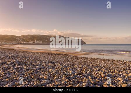 A view of Llandudno's curving shoreline lined by white fronted hotels at dusk.  The Great Orme headland is in the distance and a fading blue sky is ab - Stock Photo