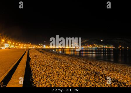 A view of Llandudno's curving shoreline lined by white fronted hotels at night.  The Great Orme headland is just visible in the distance and a night s - Stock Photo