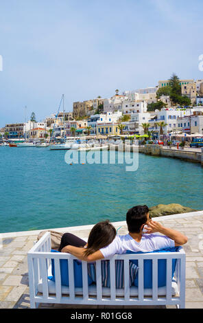 Young couple sitting on a bench on the harbour promenade enjoying the view of Naxos City and Kastro, Island of Naxos, Cyclades - Stock Photo