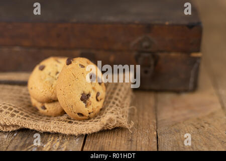 Cookies tied with a gray jute string into a bow. Cookies of sweets on a wooden kitchen table. Black background. - Stock Photo