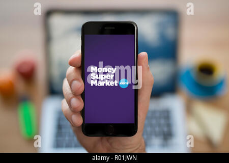 A man looks at his iPhone which displays the Money Supermarket logo, while sat at his computer desk (Editorial use only). - Stock Photo
