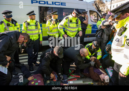 London, UK. 31st October, 2018. Police officers remove lock-on tubes from environmental campaigners blocking a road around Parliament Square after making a formal declaration of non-violent rebellion against the British government for 'criminal inaction in the face of climate change catastrophe and ecological collapse'. Credit: Mark Kerrison/Alamy Live News - Stock Photo